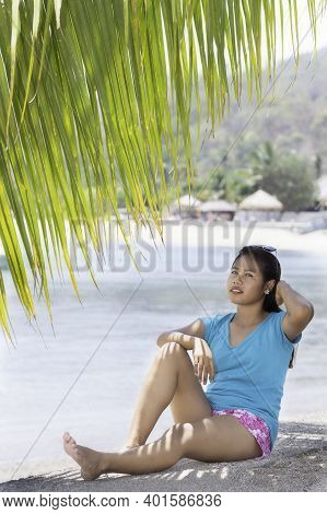 Young Indonesian Girl With Sunglasses Sitting Under A Palm Tree
