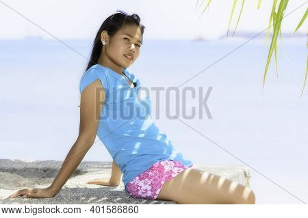 Young Indonesian Girl Sitting Under A Palm Tree