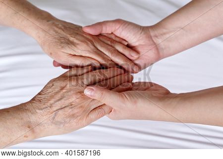 Wrinkled Hands Of Senior Woman In The Palms Of A Young Woman. Concept Of Care And Support, Elderly M