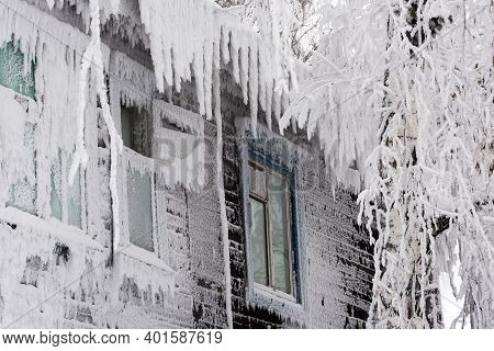Frozen Windows Of An Old Wooden Residential Building Close Up