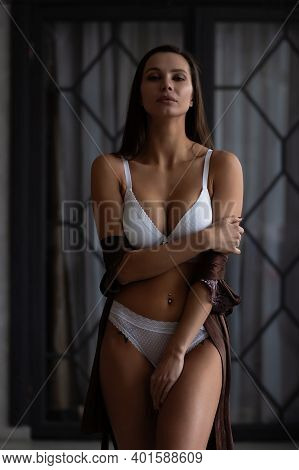 Self Assured Young Alluring Lady With Long Dark Hair Taking Off Silk Robe And Standing In Classic St