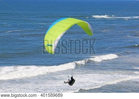 Paraglider Flying Yellow Wing Above The Beach