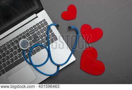 Laptop And Stethoscope With Hearts On Gray Background. Top View