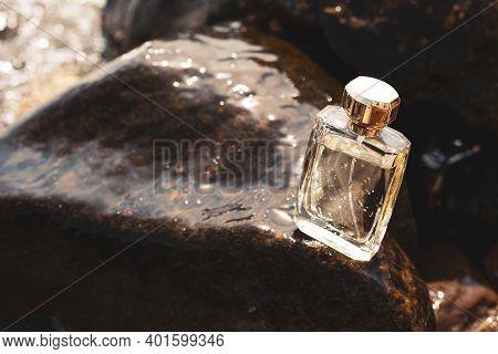 Bottle Of Perfume On Wet Stones.  Beauty Concept