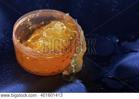 Yellow Cosmetic Gel On A Dark Background