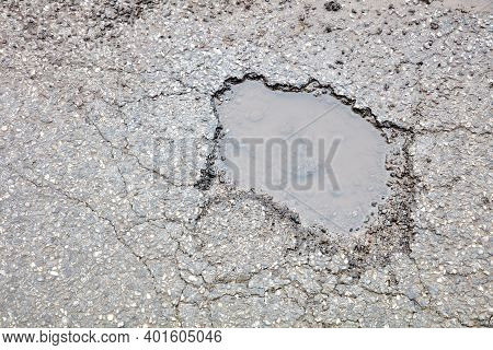 Pothole Filled With Water On A Wet Road.