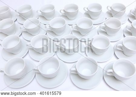 Empty Tea-drinking Utensils In Large Quantities. Catering Or Banquet Concept. White Porcelain Tea Cu