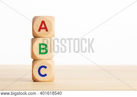 Abc Letters Alphabet On Wooden Blocks Stacked On Wood Table. White Background. Copy Space