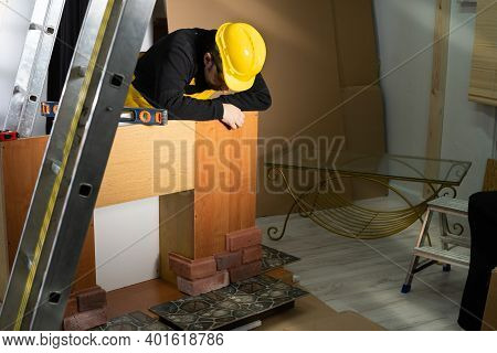 An Employee Leans Against The Cupboard And Looks Down At The Glued Brick-shaped Decorative Tiles. An