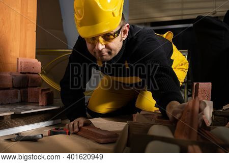Every Now And Then A Manual Worker Reaches For The Next Element Of The Decorative Brick In Order Not