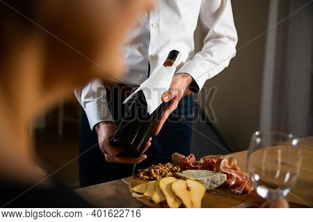 A Man In A White Shirt Presenting Guests A Bottle Of Red Wine. Wine Tasting With Tapas, Meat Board,