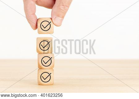 Checking Or Checklist Concept. Hand Picked Wooden Cube Block With Check Icon Stacked On Wooden Table