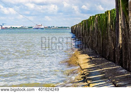 Beach Of Breskens With Wooden Poles And The Industry Of Vlissingen In The Distance, Zeeland, The Net