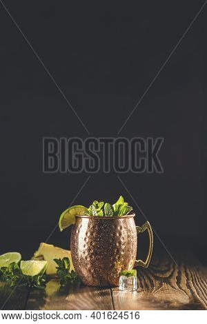 Moscow Mule Alcoholic Cocktail In Copper Mug With Crushed Ice, Mint And Lemon Over Minton Dark Woode
