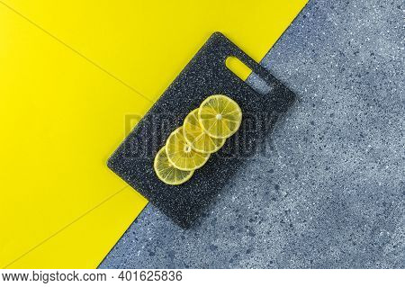 Creative Food Background Of Ultimate Gray And Illuminating Trending Color. Lemon And Cutting Board O