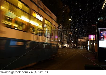 Close-up Of Tram With Pedestrian In The Dark Evening. Bahnhofstrasse At Christmastime In Time Of Cor