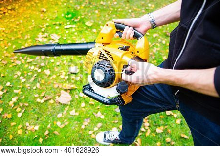 Using A Cordless Leaf Blower In A Garden. Cleaning A Lawn.
