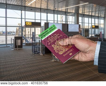 Mockup Of Airport Terminal With Businessman Hand Holding British Passport And Vaccination Certificat