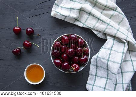 Tasty Cherries And Natural Honey On Black Concrete Background, Top View.