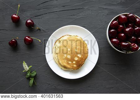 Delicous Pancakes And Ripe Tasty Cherriers On Black Concrete Background, Top View.