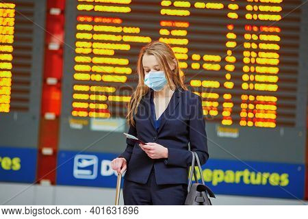 Woman Wearing Protective Face Mask With Hand Luggage In International Airport Terminal, Looking At I