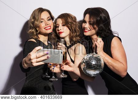 Celebration, party and emotion concept - Three fashionable young women dressed in black cocktail dresses are singing with a microphone, holding disco balls, glasses of champagne and smiling