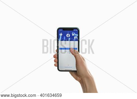 Mykolaiv, Ukraine - July 9, 2020: Woman Holding Iphone 11 With Facebook App On Screen Against White