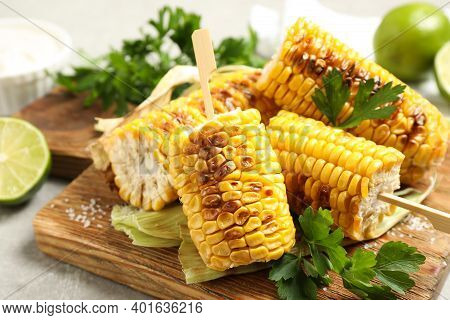 Tasty Grilled Corn Cobs With Parsley On Wooden Board, Closeup