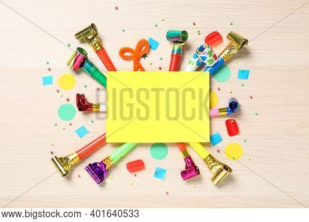 Flat Lay Composition With Party Blowers And Blank Card On Wooden Background. Space For Text