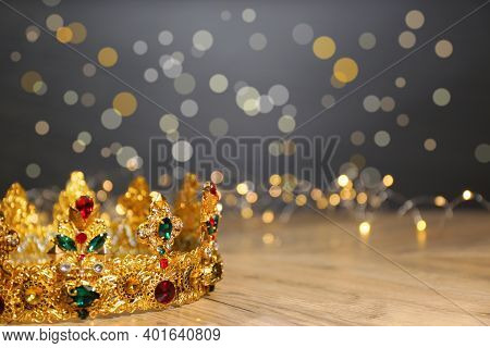 Beautiful Golden Crown With Gems And Fairy Lights On Wooden Table, Space For Text. Fantasy Item