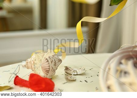Broken Bauble On White Table. Mess After New Year Party