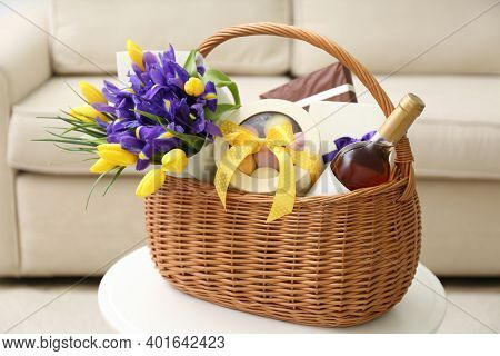 Wicker Basket With Gift, Bouquet And Wine On White Table Indoors