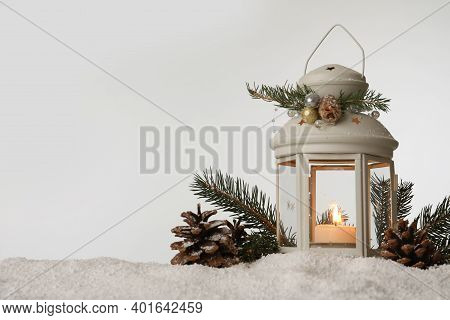 Decorative Lantern And Christmas Decor On Snow Against Light Grey Background. Space For Text