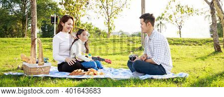 Happy Family Picnic. A Little Girl Playing Ukulele With Her Parents (father, Mother) During Picnicki