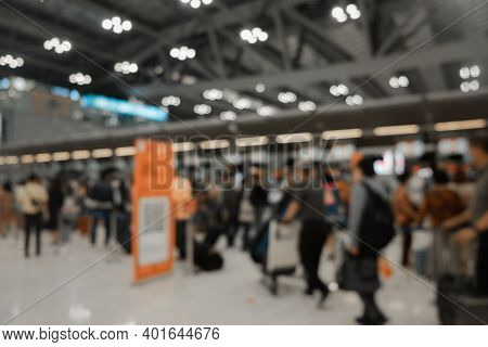 Blur Background Of Airport Check-in Counters With Many Passengers And Light Bokeh