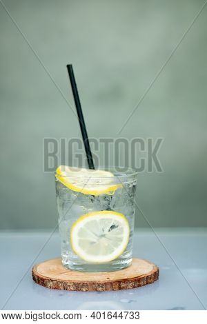 Glass Of Ice And Water Decorated With A Slice Of Lemon With Black Straw On Wood Saucer