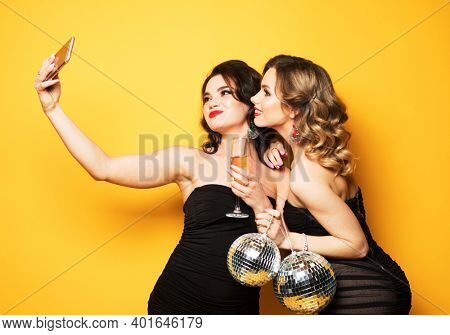 Celebration, party, and people concept - two fashionable young women wearing black cocktail dresses holding disco balls and make a selfie.