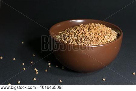 Brown Uncooked Buckwheat In A Bowl With Scattered Grains Nearby On A Black Background