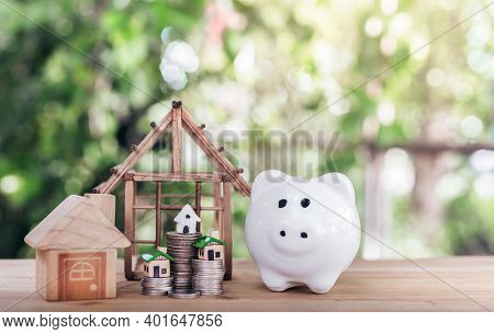 Piggy Bank Is Placed On The Table And House Placed On A Coin. Concept Calculating To Buy A Home. Pla