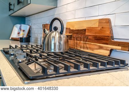 Five Knobs Kitchen Cooktop With Kettle Over The Burners And Cast Iron Grate
