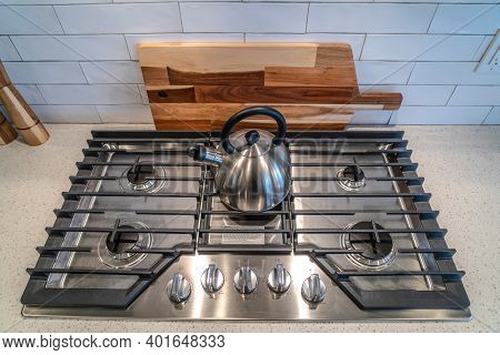 Kettle Over Burners And Grate Of A Cooktop Built Into The Kitchen Countertop