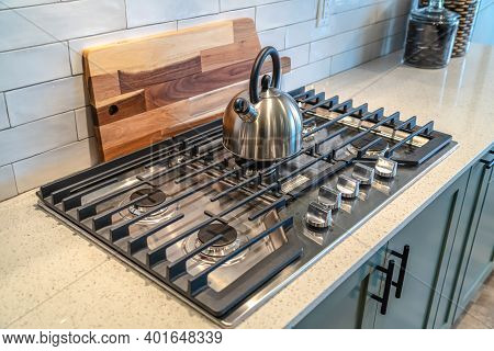 Kettle Over Five Burner Cooktop Built Into The Kitchen Countertop With Cabinets