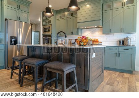Kitchen Island With Stools Against Cabinets Refrigerator And Cooktop Background