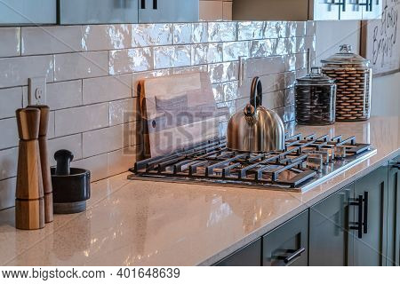 Cozy And Clean Kitchen Interior With Cooktop And Cooking Tools On The Countertop