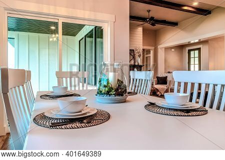 Dinner Table Set For Four Persons With Tableware Around A Candle Centerpiece