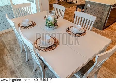 Dinner Table With Tableware For Four Persons Arranged Around Candle Centerpiece