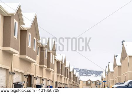 Two Storey Townhouses With Sliding Windows And White Garage Doors Against Sky