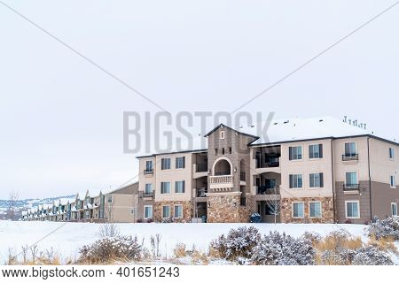 Apartments And Townhouses On A Scenic Snowy Neighborhood Landscape In Winter