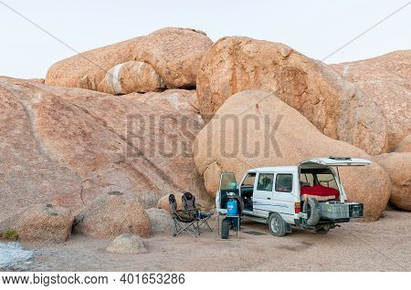Spitzkoppe, Namibia - June 18, 2012: Camping At The Greater Rock Arch At Spitzkoppe. A Vehicle And C