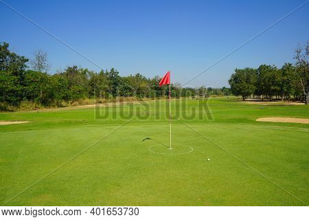 Red Flag At The Beautiful Golf Course At The Sunrise Time. Beautiful Golf Course In A Sunny Day. Bac